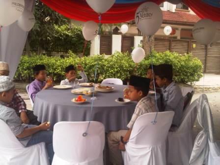Anak2 RASR sedang duduk di meja makan di bawah khemah yang dipasang di depan RASR.